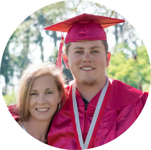 A portrait of a young man wearing a pink graduation gown with his mom on his side.