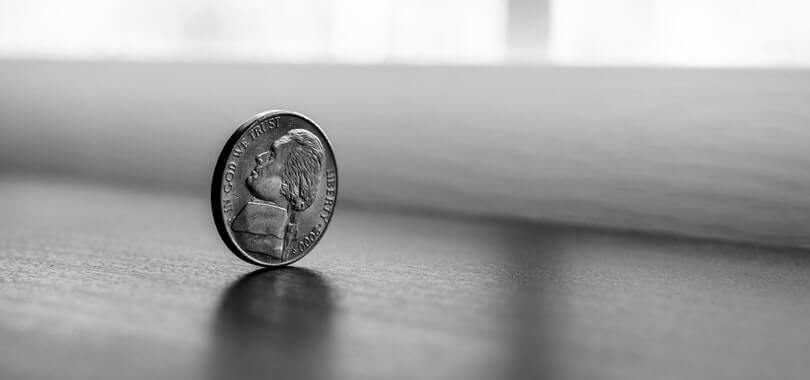 A nickel balancing on a table.