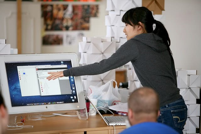 A girl pointing her hand to the monitor while a bald man watching her from the foreground.