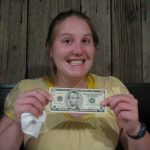 a girl holds a money related to student loan forgiveness