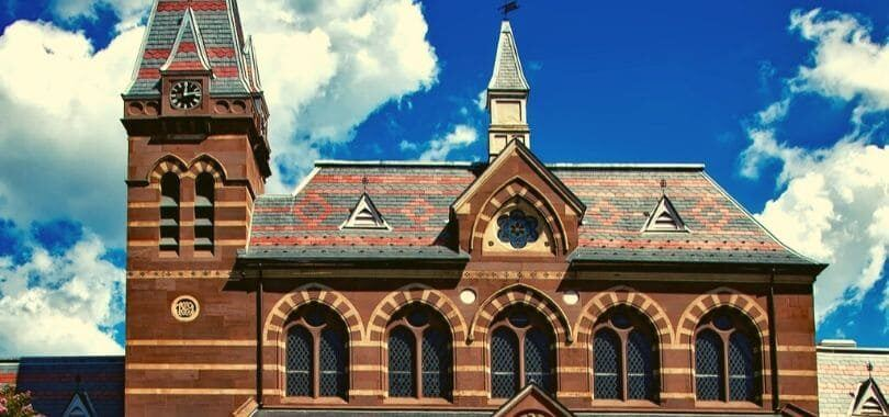 A brown college building with a clock tower on the side of the building.