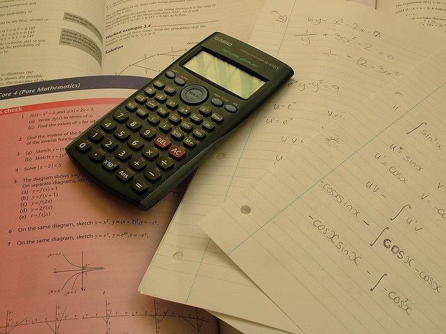 Casio calculator placed over a math book and notes.