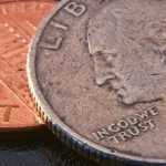 A quarter laying on top of a penny.