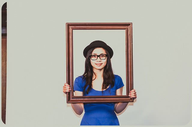 A girl holding a picture frame in front of her.