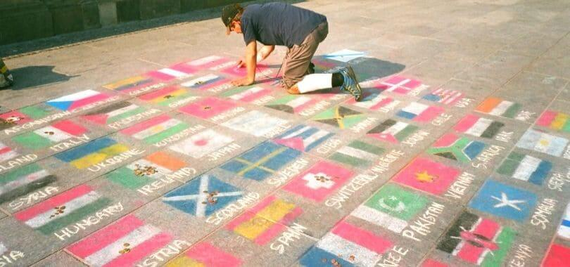 A person drawing various flags on the ground.