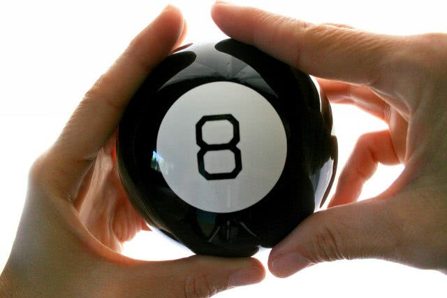Both hands holding a number 8 billiard ball.
