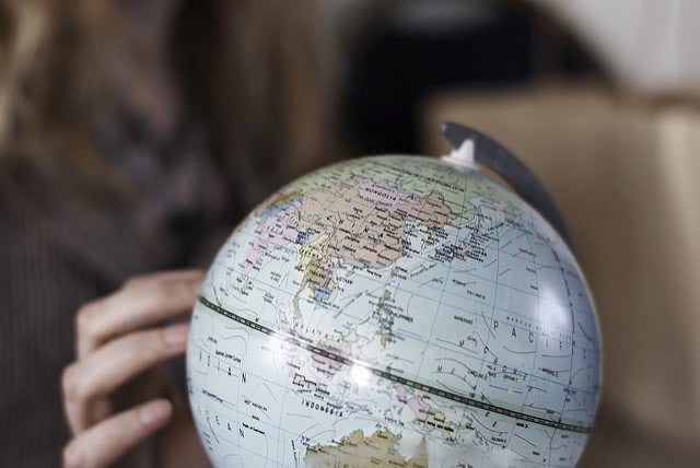 Girl's hand touching a globe figure.