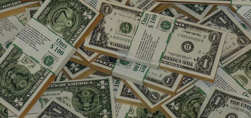 Stacks of dollar bills piled on top of each other.