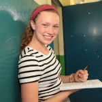 A girl smiling while holding a ballpen and notebook with both hands.