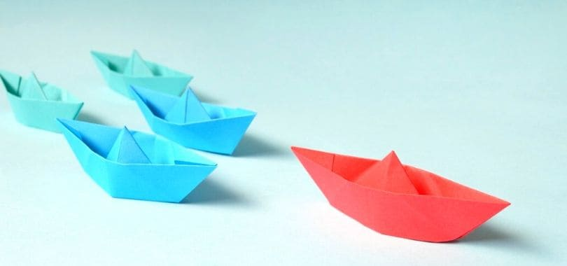 Paper boats on a surface, with one paper boat leading the others.