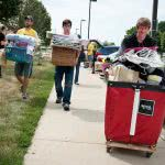 Three college students are carrying their dorm supplies while moving into college.