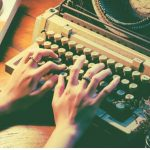 A person typing on a typewriter.
