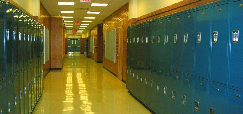 An empty high school hallway with blue lockers lining the walls.