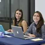 Two smiling female students with their laptops on the desk.