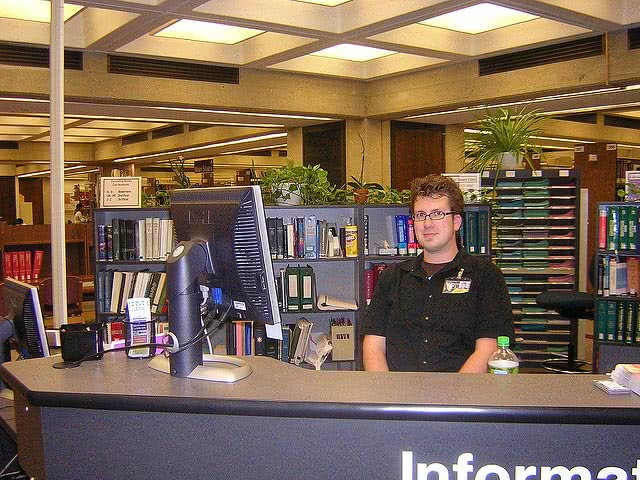 Student working at a library as part of their work study programs