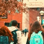 Students wearing backpacks walking on campus.