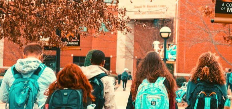 Students wearing backpacks walking on campus.