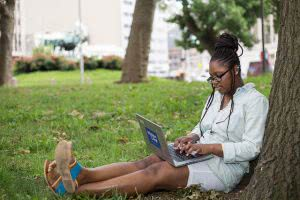 A student writes her college app essay on her laptop