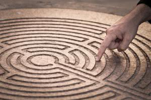Finger pointing at a maze - it helps to know where to begin with your student loan repayments
