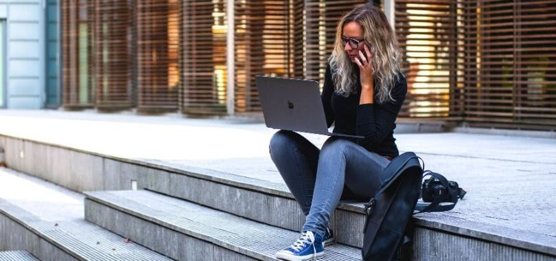 A college student sitting on steps while talking on the phone and typing on her laptop.