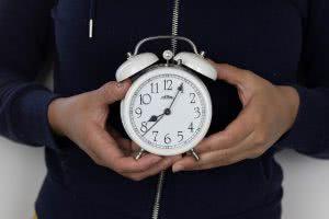 A student holding an alarm clock.