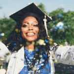 A student wearing a graduation cap throwing confetti at the camera while she smiles.
