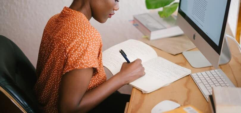 A woman sitting in front of a computer writing in a notebook.