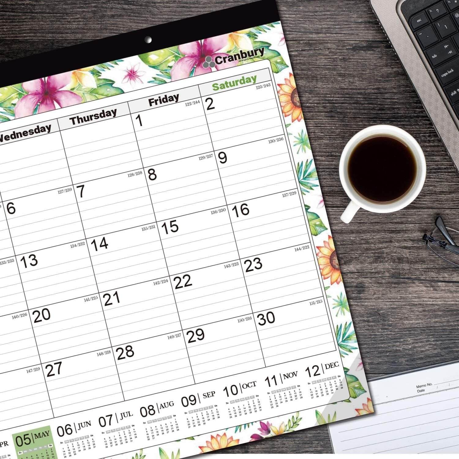 A floral desk calendar with a cup of coffee next to it.
