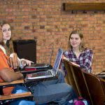 Three students in a lecture hall discuss Credible student loans