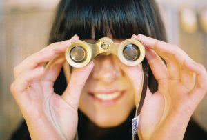 Woman holding binoculars - how do scholarships work? we can help you search