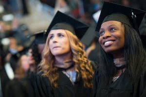 Two students at graduation have to start thinking about paying back student loans