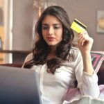 A woman sitting on a couch holding a yellow credit card.