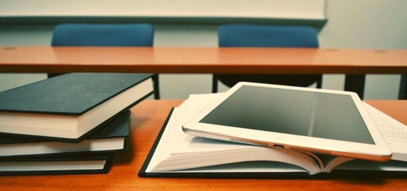 Textbooks on a desk with an iPad laying on an open textbook.