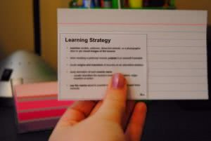 Student holds up her flashcard as she studies for the SAT test