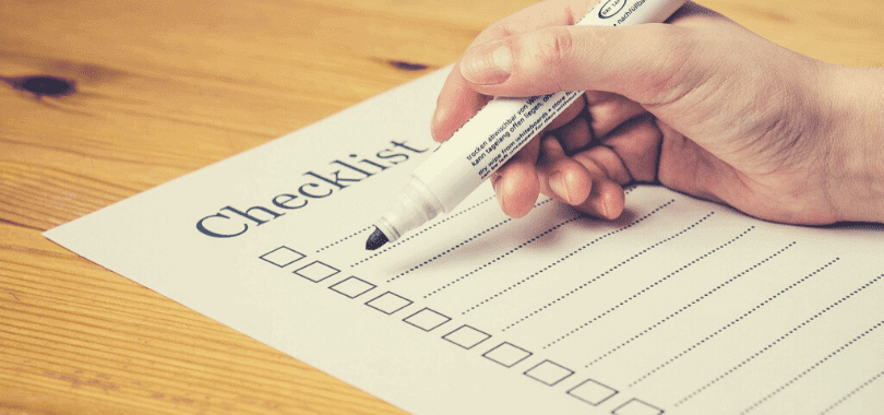 A person holding a marker against a blank checklist.
