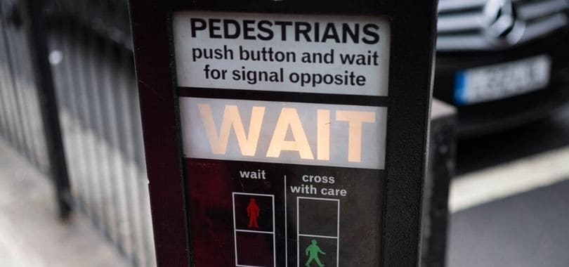 """A pedestrian crossing button that says """"wait."""""""
