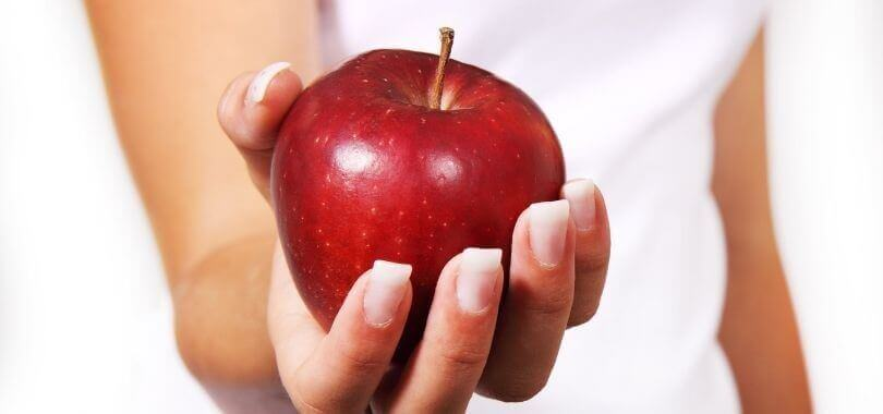 College student holding an apple