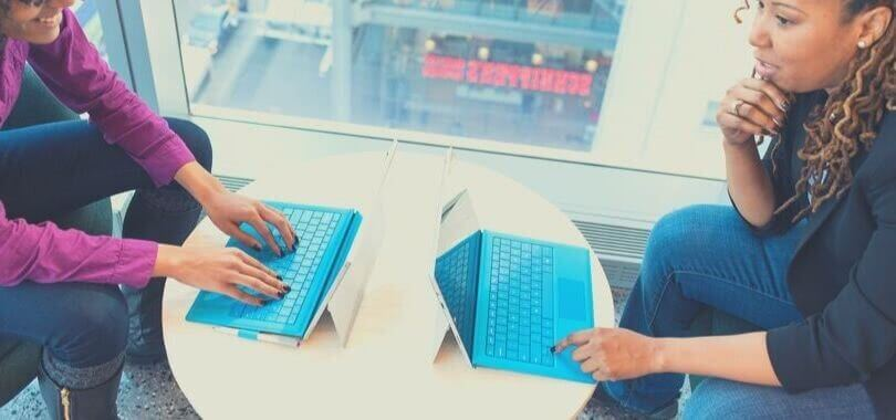 Two computer scientists discussing over their blue laptops.