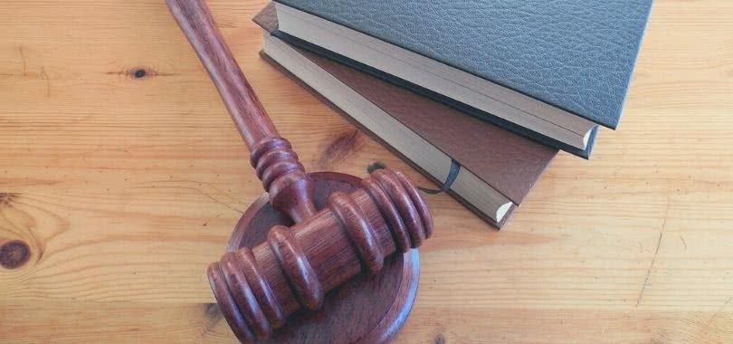 Gavel and two law books on wooden table.