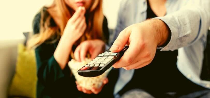 One college student eats popcorn while the other holds a remote while they watch TV.