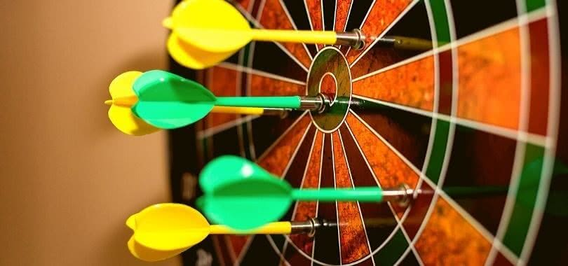 Yellow and green darts on a target board.
