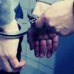 An officer handcuffing a criminal