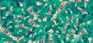 Money bills falling over a green marble background.