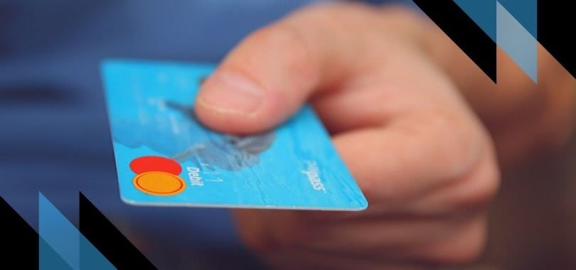 A hand holding a blue credit card.