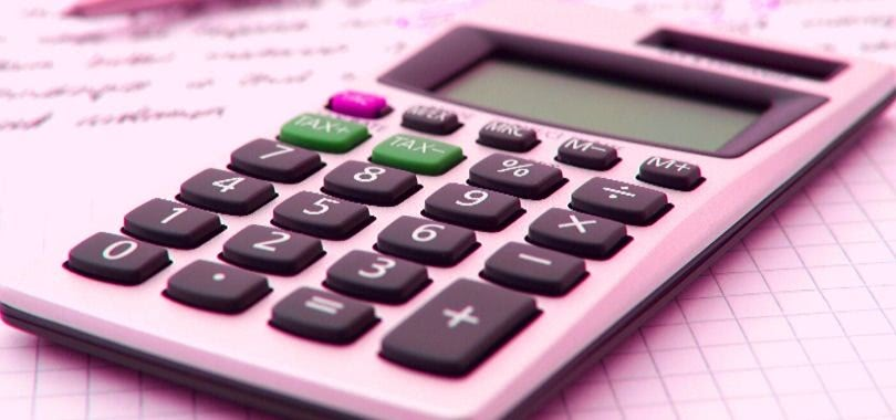 A calculator sitting atop loan documents.