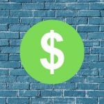 Dollar sign on a brick college wall.
