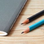Two pencils on a desk next to a gray boolet.