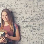 High school student with books standing in front of a whiteboard filled with math formulas.